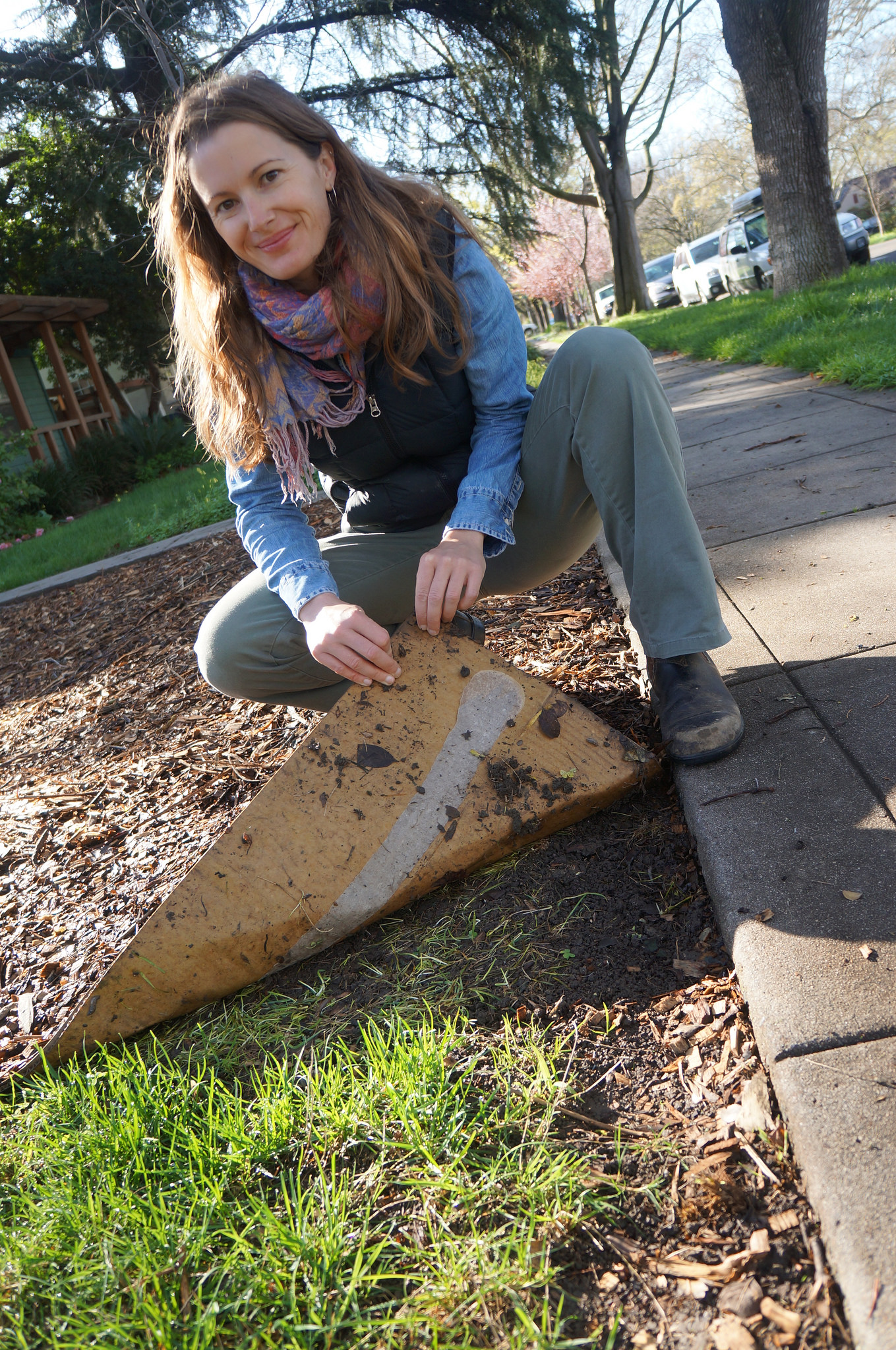 Image of Stacey Parker lifting up cardboard to reveal a lawn free patch.