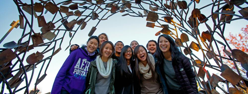 Image of students underneath the shovel sculpture located in the Arboretum GATEway Garden