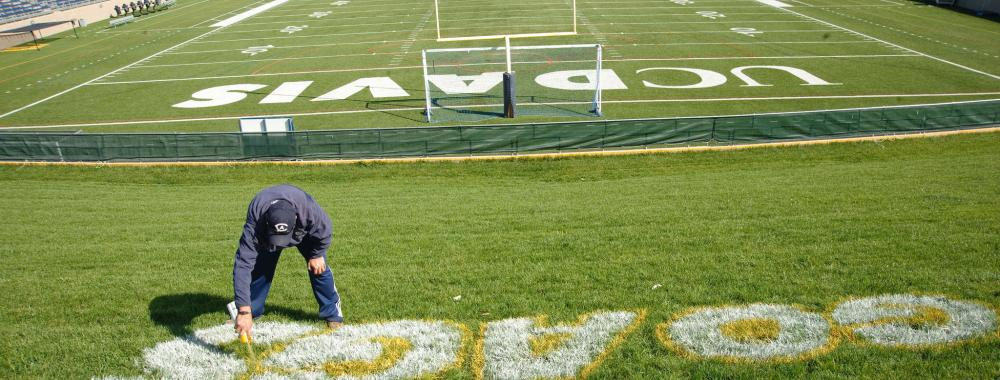 Image of staff from UC Davis Grounds and Landscape Services' sports turf team spray painting the football field.