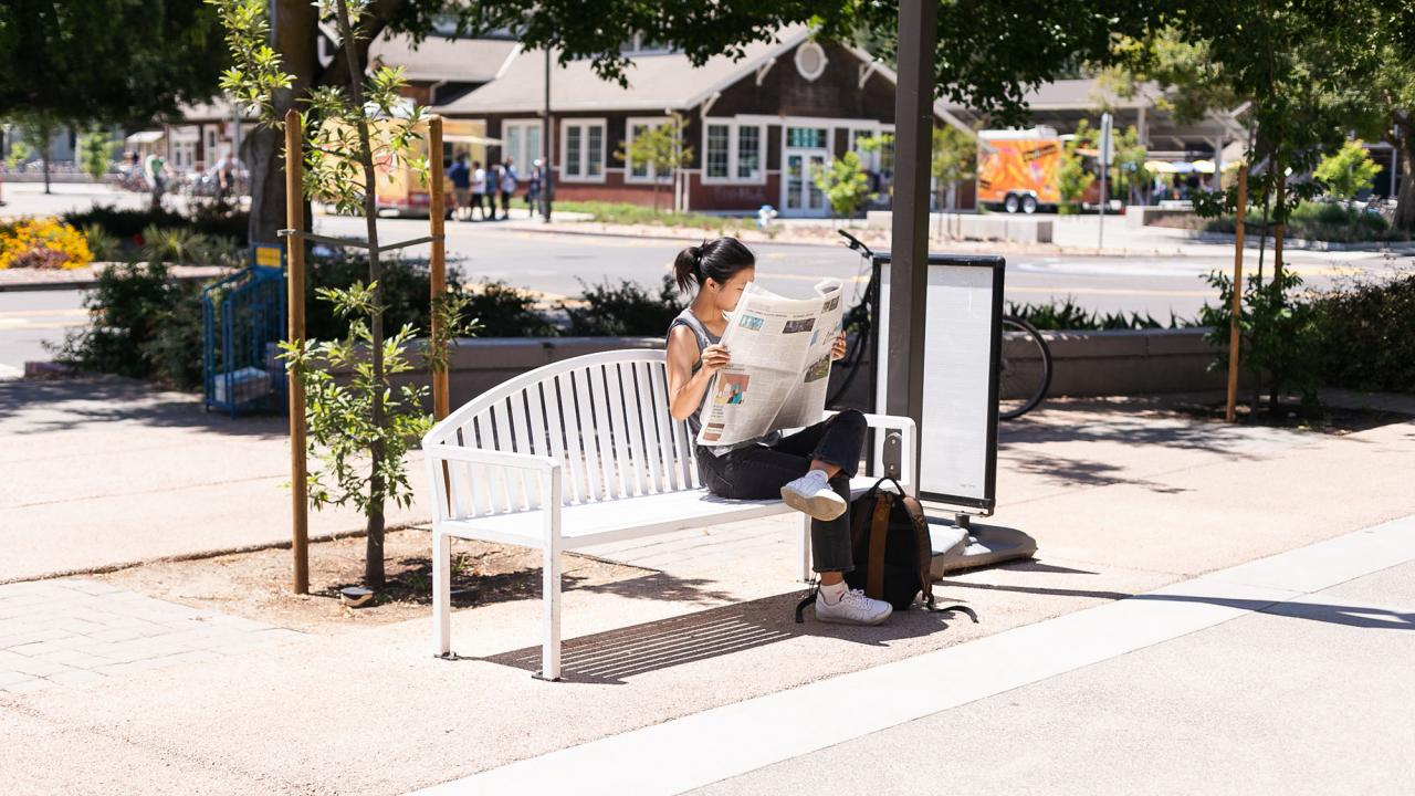 person reading the newspaper on a bench