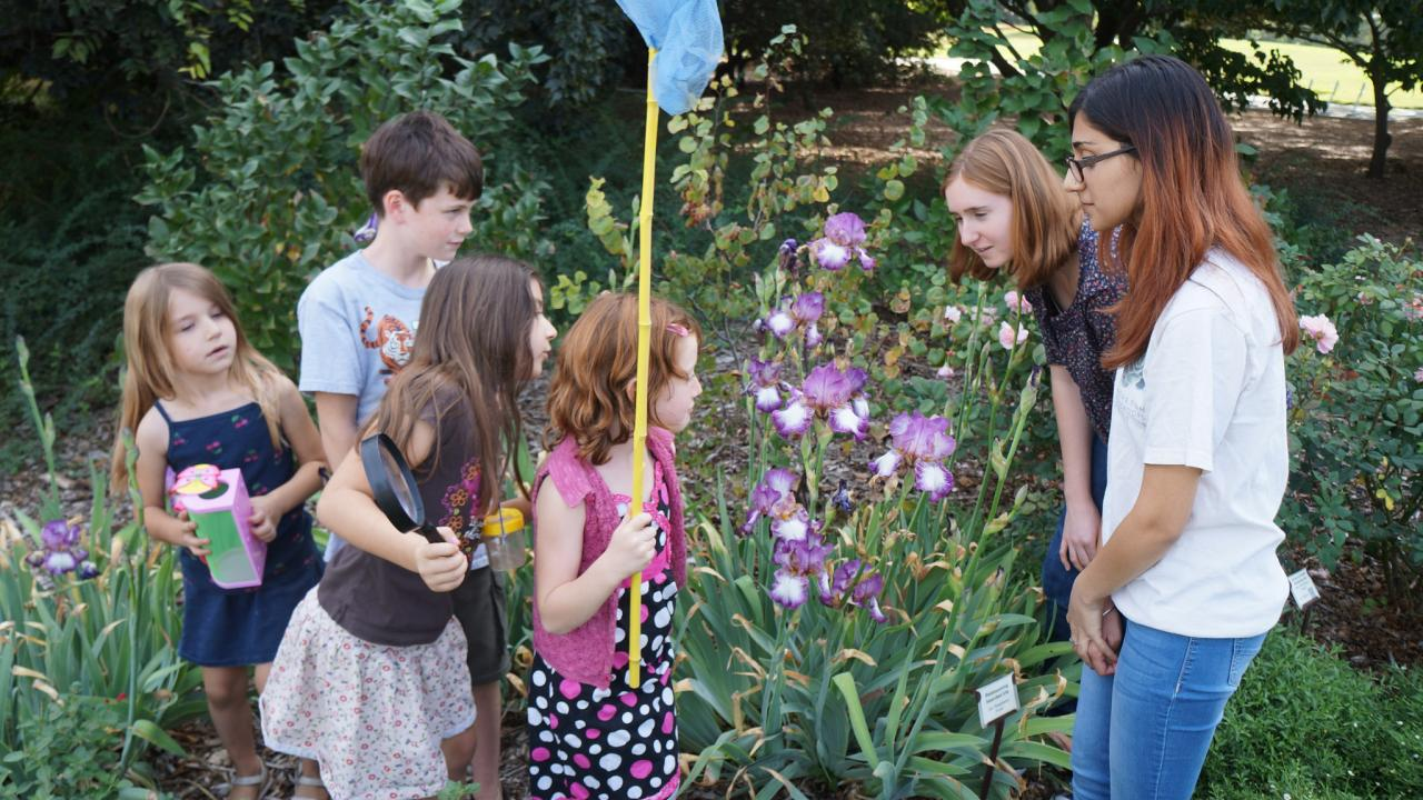 Image of Arboretum Ambassadors with children in the Nature's Gallery Court garden.