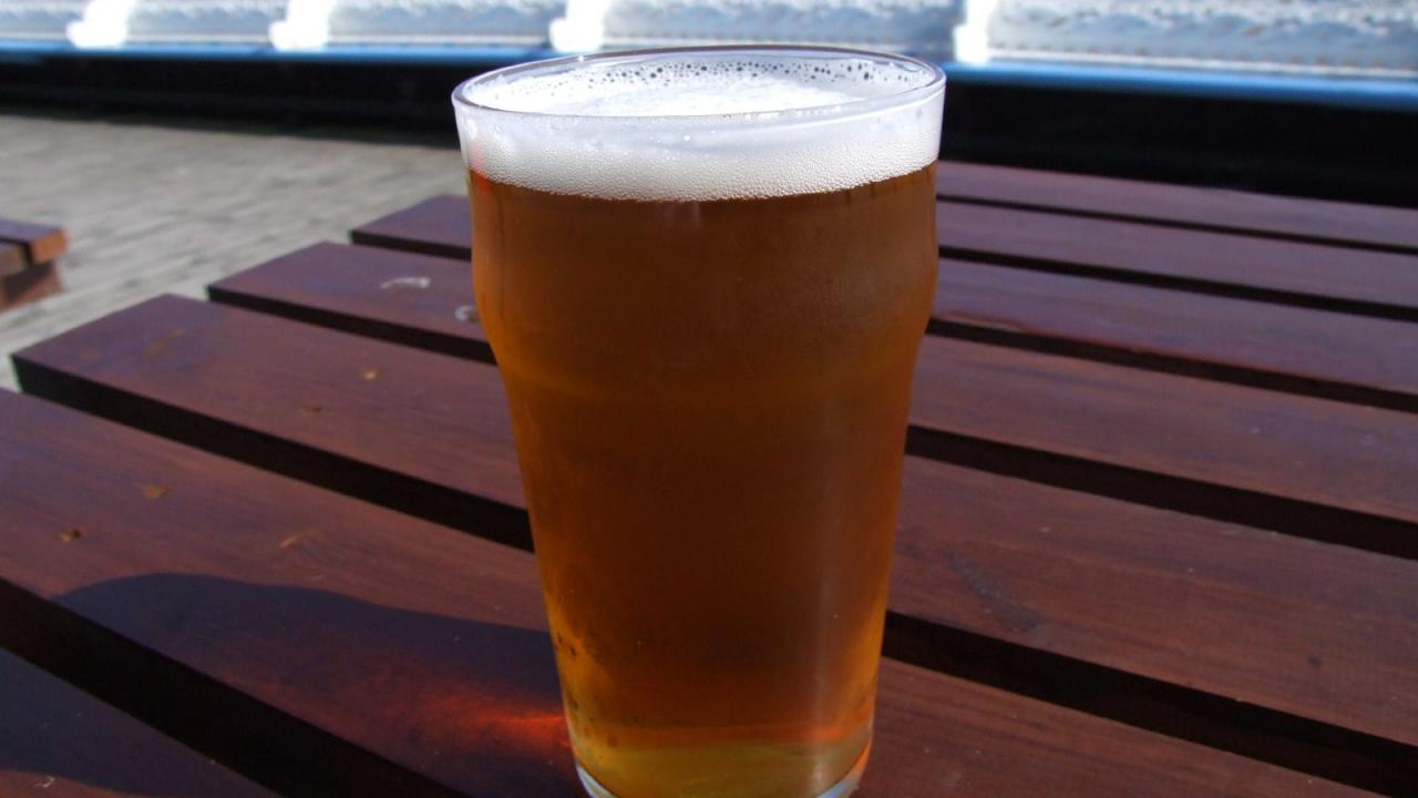 Image of a pint beer on a picnic table.