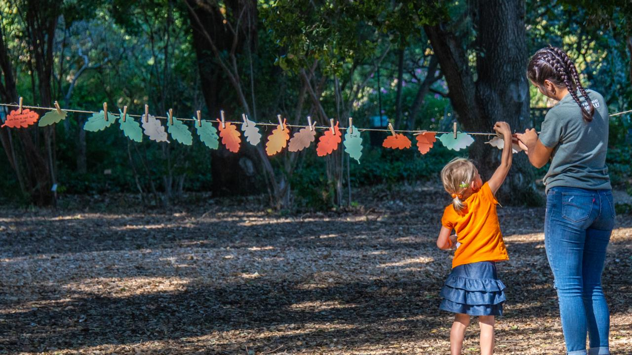 Image of student helping child place oak leaves on a clothesline.