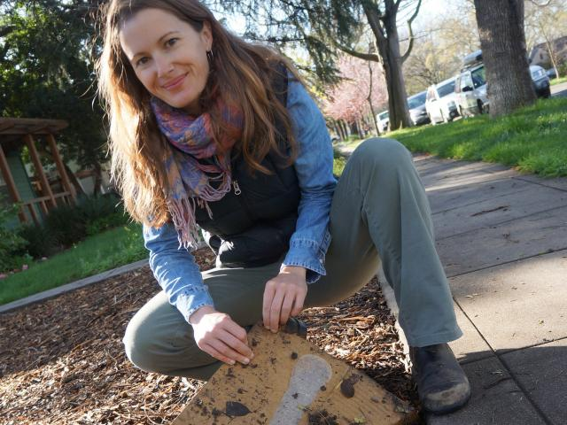 Image of Stacey Parker and the cardboard she used to remove her front lawn.