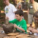 Image of young man learning how to grind acorns.