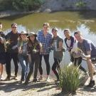 Students on the Learning by Leading Waterway Stewardship team plant sedges and rushes along the newly created banks of the Arboretum Waterway.
