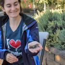 Image of a student researcher preparing to release a hummingbird after conducting a brief health exam. The Arboretum Teaching Nursery is a research station for a large hummingbird health research project sponsored by UC Davis Hummingbird Health and Conservation Program.