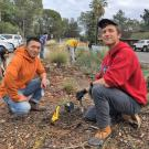 Program co-coordinators Chris Huang and Cameron Long take a break from planting a new plant to pose for a photo, kneeling with the landscape in the background.