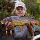 Peter Moyle, associate director of the Center for Watershed Sciences, poses with a common carp.