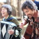 Folk musicians play instruments and laugh