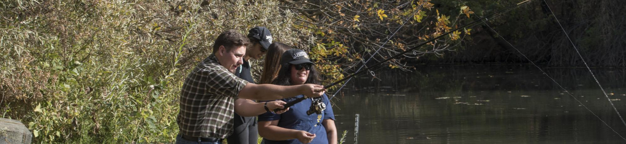 Image of students being taught how to fish at UC Davis Putah Creek Riparian Reserve.